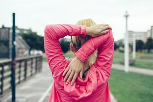 Unrecognizable woman stretching arms before training outdoors