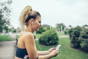 Woman with earphones listening music in smartphone