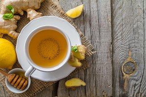 Ginger tea and ingredients on rustic wood background