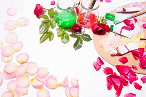Paints and brushes with rose petals