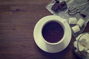 Hot chocolate in white cup, wood background