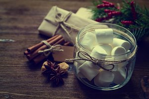 Christmas decorations - marshmallow spices presents, tree, wood background