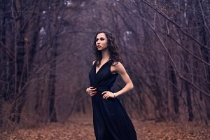girl in a black dress in the woods