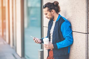 Man with smartphone and coffee cup