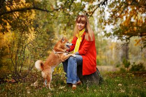 Girl with Shiba Inu dog in park