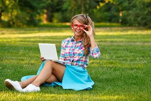 Girl with laptop adjusts glasses