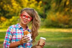 Girl hold cup of coffee and hotdog