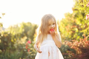 Little girl eating a tomato.
