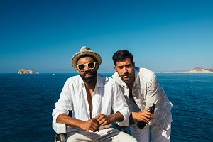 stylish men posing against ocean