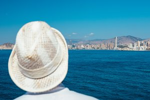 Person in straw hat looks cityscape