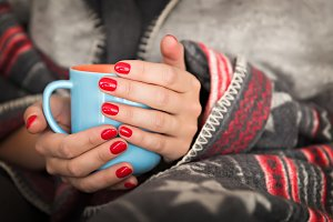 Female hands holding a blue mug.