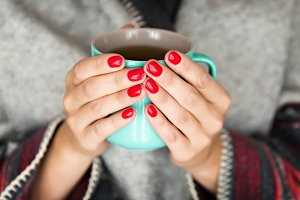 Female hands holding a green mug.