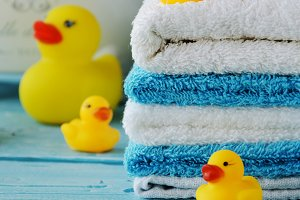 stack of colorful towels and bath duck on the table