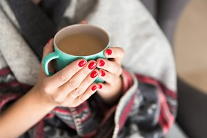 Female hands holding a mug.