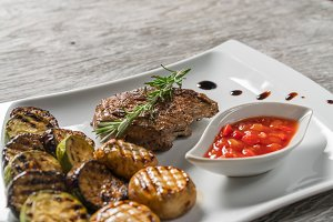 Appetizing stake on white plate. Grilled meat