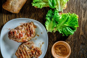 Grilled steak with herbs on a wooden background