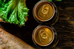 Two cans of beer on a wooden background.