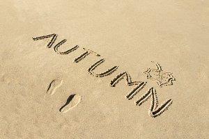 Autumn word written on beach sand