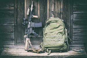 Tactical carbine and green backpack on the steps of the old house, vintage faded