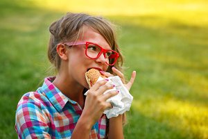 Pretty girl eating a hot dog.