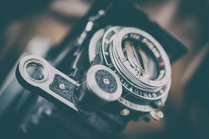 Close-up of the lens of retro folding camera close-up, vintage faded, shallow depth of field
