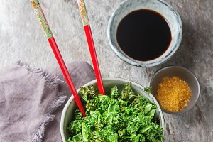 Fried Kale cabbage with soy sauce. Japanese chopsticks, spices. Grey stone background. Top view