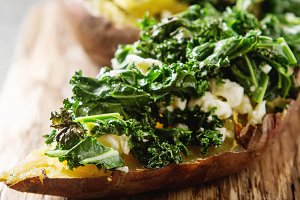 Baked sweet potatoes with kale, Cheddar cheese. Vegetarian food. Grey stone background.