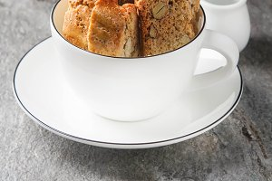 Traditional Italian food. Cantuccini cookies in white mug. Gray stone background.