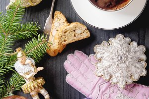 Traditional Italian food. Christmas toys. Cantuccini cookies with black coffee in a white mug, milk. Dark wood background.