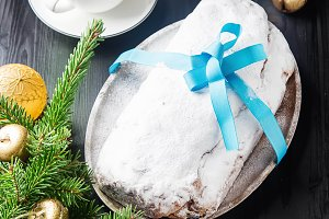 Christmas stollen on a silver tray with a white cup of hot coffee, a fur-tree branch Christmas toys, santaklaus and blue balloons. Dark wood background.