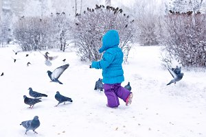 Cute little girl frightening pigeons