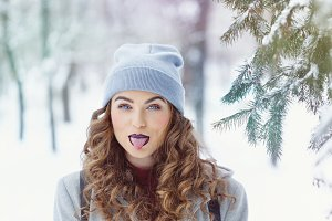 Hipster Girl winter. Show tongue