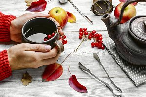 Palm of your hand with cup of autumn tea