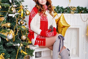 Girl in stockings at Christmas tree