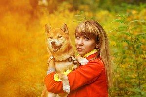Girl hugs a dog Shiba Inu