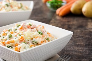 Russian salad on rustic wooden