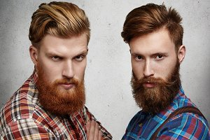 Beauty and fashion. People and friendship. Close up shot of two attractive fashionable Caucasian friends with stylish haircuts and big beards posing together against white studio wall. Horizontal