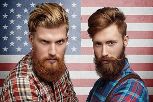 Emotions, patriotism, citizenship and people. Two serious and confident American patriots with stylish haircuts and beards, posing against US flag. Portrait of Caucasian friends in hipster shirts