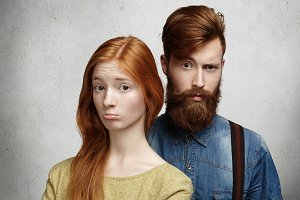 People and relationships. Young Caucasian couple with unhappy look squabbling. Sad and sulky girl with long red hair pushing out her lower lip and pouting while her confused boyfriend standing behind
