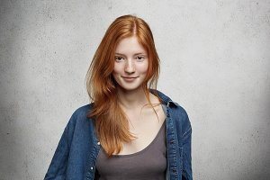 Youth and happiness. Close up view of beautiful Caucasian teenage woman with long ginger hair and freckles, dressed casually, standing against blank gray wall. Horizontal, isolated, studio shot, model
