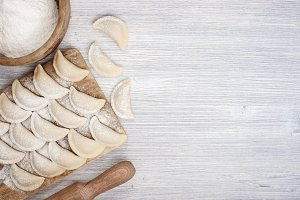 Wooden background with raw dumplings