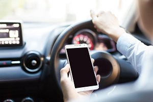 man using phone while driving the car (selective focus) - transportation and vehicle concept
