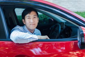 Portrait of Asian Business Man Driving His Red Car