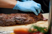 Butcher Cutting Medium Rare Beef on Cutting Board in the Kitchen