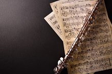 Flute and score on black table top