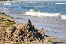 Sandy castle on sea beach.
