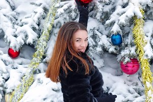 Girl decorates Christmas tree toys