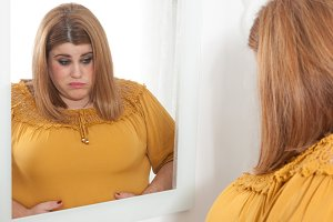 Overweight woman into the mirror