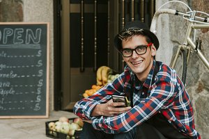 young businessman with mobile phone at the door of your business