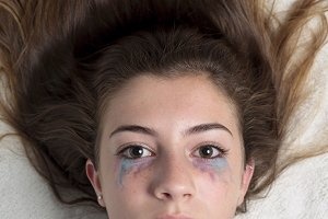 Teen girl lying with  painted eyes.